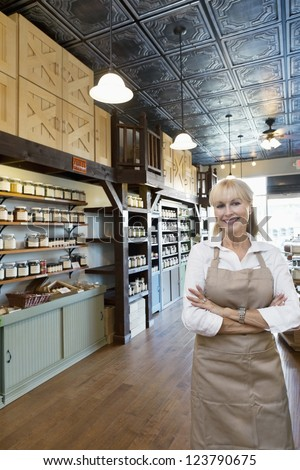 Portrait of a happy senior female spice merchant standing with arms crossed in store - stock photo