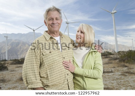 Portrait of a happy senior male standing with wife during vacation at wind farm