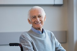 Portrait of a happy senior man sitting on wheelchair in rehabilitation center. Cheerful old man sitting on wheelchair at hospital. Disabled man in his wheelchair looking at camera.