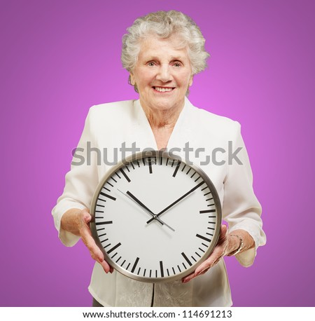 portrait of a happy senior woman holding clock over purple
