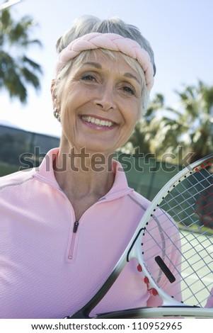 Portrait of a happy senior woman holding tennis racquet