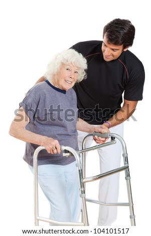 Portrait of a happy senior woman holding walker while trainer assisting her over white background - stock photo