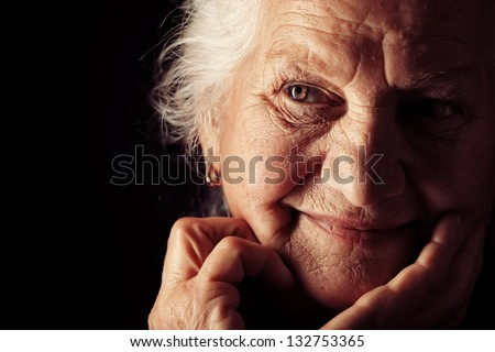 Portrait of a happy senior woman smiling at the camera. Over black background. Stock photo ©