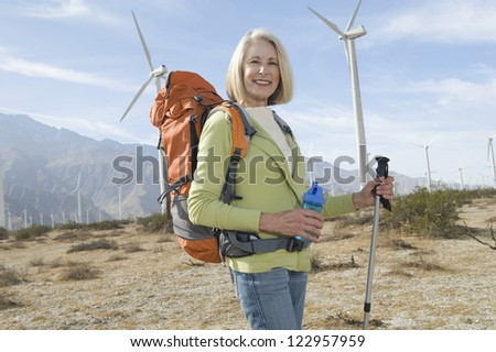 Portrait of a happy senior woman standing with trekking pole and backpack at wind farm