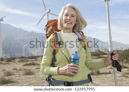 Portrait of a happy senior woman standing with trekking pole and bottle at wind farm