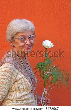 Portrait of a happy senior woman with a white rose over an orange wall.