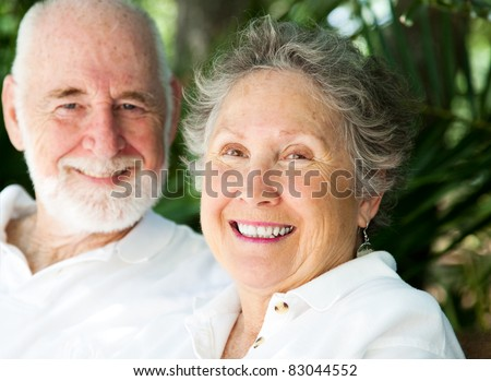 Portrait of a happy senior woman with her loving husband in background.