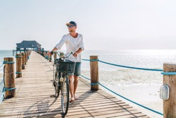 Portrait of a happy smiling barefoot man dressed in light summer clothes and sunglasses walking with a bicycle on the wooden sea pier. Careless vacation in tropical countries concept image.