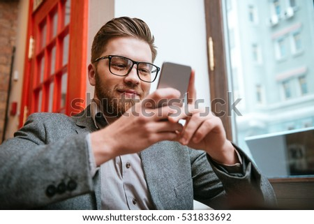 Portrait of a happy smiling businessman in eyeglasses using smartphone while sitting at the office #531833692
