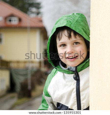 Portrait of a happy smiling child boy in a raincoat in the rain.