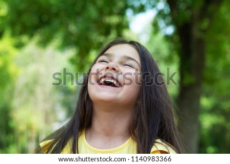 Portrait of a happy smiling child girl outdoor. Cute little girl playing in the park. Laughing child. Expressive facial expressions.