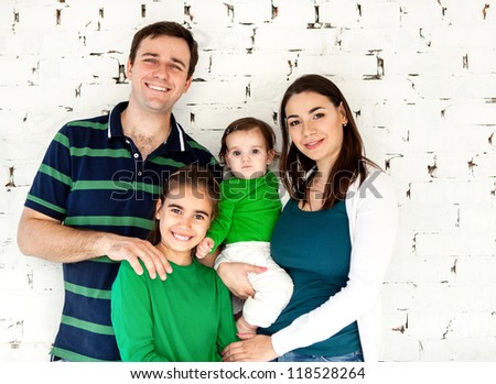 Portrait of a happy smiling family near white brick wall