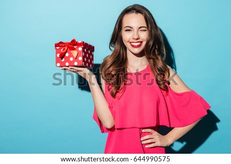 Portrait of a happy smiling girl in dress holding present box and winking isolated over blue background
