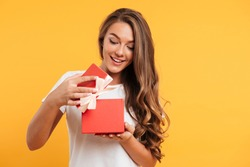 Portrait of a happy smiling girl opening a gift box isolated over yellow background