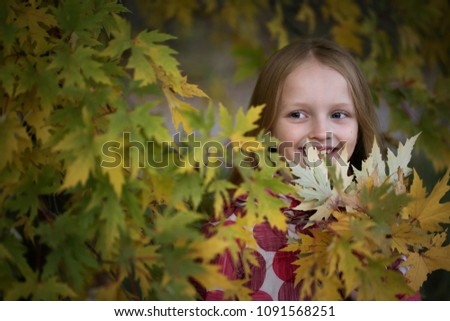 Stock Photo Portrait of a Happy smiling little girl in the autumn park. Cute four years old child enjoying nature outdoors.