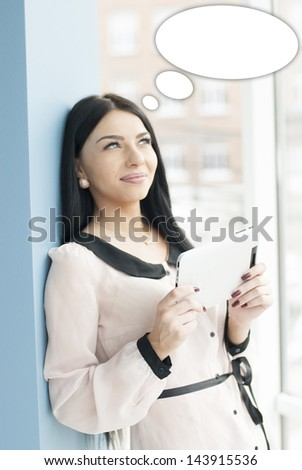 Portrait of a happy smiling young business woman using tablet PC while standing relaxed near window at her office with dialogue box above her