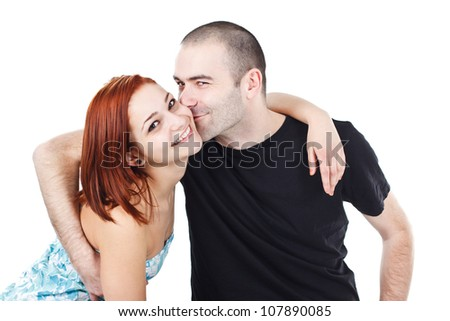 Portrait of a happy, smiling young couple,man kissing woman`s face - isolated on white