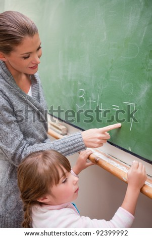 Portrait of a happy teacher and a pupil making an addition on a blackboard