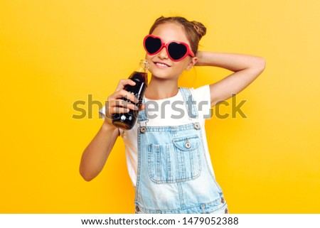 Portrait of a happy teenager girl on a yellow background with a refreshing drink in her hand