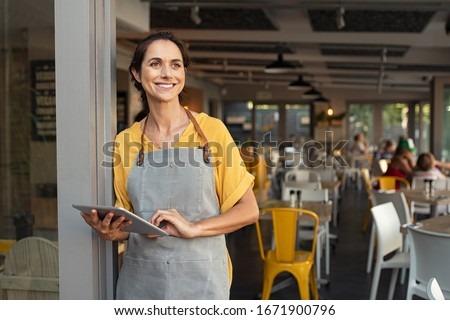 Portrait of a happy waitress standing at restaurant entrance holding digital tablet. Happy mature woman owner in grey apron standing at coffee shop entrance leaning while looking away with copy space.