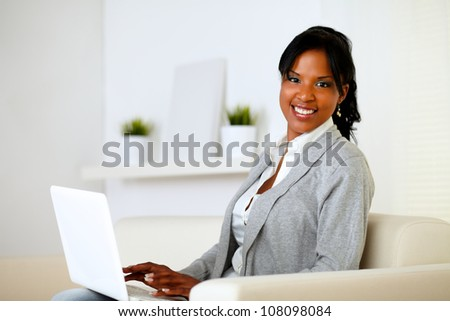 Portrait of a happy woman browse the Internet on laptop while is sitting on sofa at home - stock photo