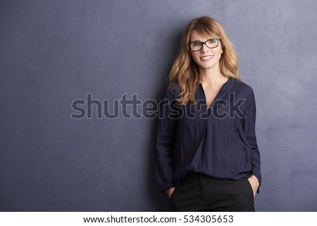Portrait of a happy woman posing against a grey background while lying against the wall.