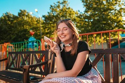 Portrait of a happy woman sitting on a Park bench listening to a voice message on her smartphone. The concept of social dependence and modern technologies.