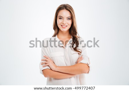 Portrait of a happy woman standing with arms folded isolated on a white background