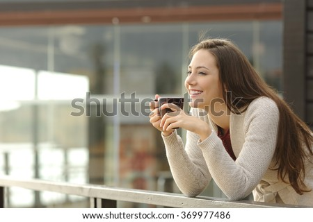 Shutterstock Portrait of a happy woman thinking and looking away at breakfast on vacation with a resort or hotel on the beach in the background