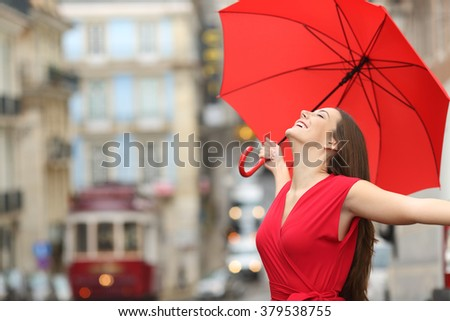 Stock Photo Portrait of a happy woman wearing red blouse under an umbrella breathing in the street of and old town in a rainy day