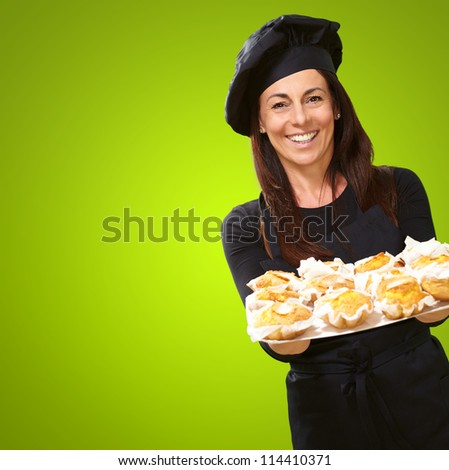 Portrait Of A Happy Woman While Holding Cupcake On Green Background