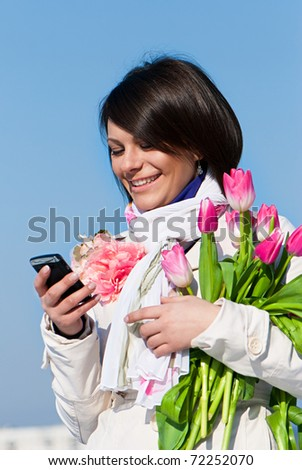 Portrait of a happy women with pink tulips typing a text message on cellphone