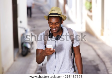 Portrait of a happy young african american man walking in town with mobile phone #295487375