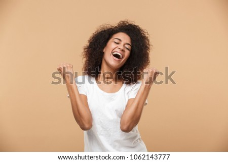 Portrait of a happy young african woman celebrating success isolated over beige background