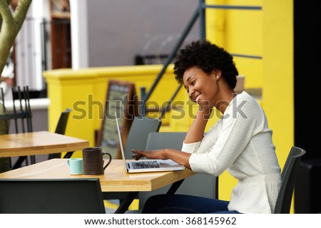 Portrait of a happy young african woman relaxing in outdoor cafe and using a laptop
