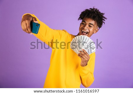 Portrait of a happy young afro american man in sweatshirt isolated, showing money banknotes, taking selfie