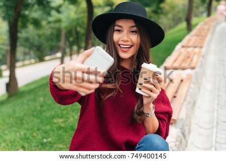 Portrait of a happy young asian girl dressed in hat and sweater holding coffee cup while sitting on a bench and taking a selfie outdoors