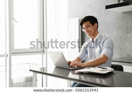 Portrait of a happy young asian man using laptop computer while sitting at the table with paperwork at home