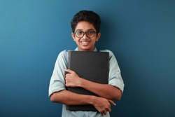 Portrait of a happy young boy holding a laptop in hand