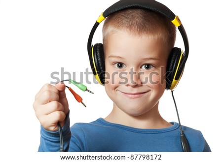 Portrait of a happy young boy listening to music on headphones against white background