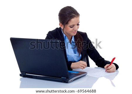 Portrait of a happy young business woman at the office desk writing against white background