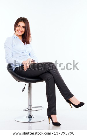 Portrait of a happy young business woman in blue shirt sitting on the modern chair against white