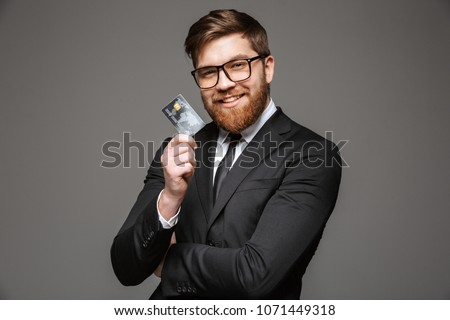 Portrait of a happy young businessman holding credit card isolated over gray background