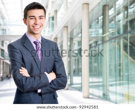Portrait of a happy young businessman in suit standing at office