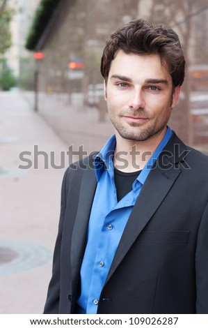 Portrait of a happy young businessman in suit standing outside office #109026287