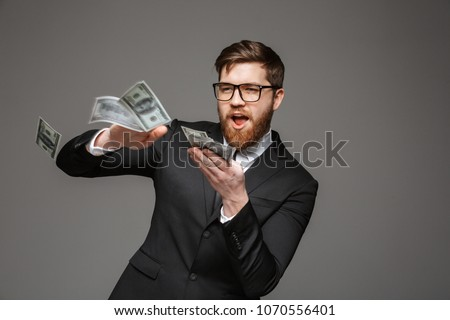 Portrait of a happy young businessman throwing out money banknotes isolated over gray background