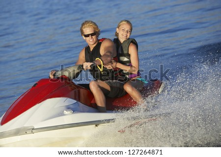 Portrait of a happy young caucasian couple riding jet ski on lake