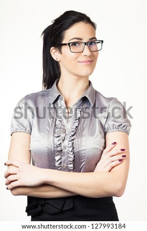 Portrait of a happy young confident business woman standing with folded hands against white background
