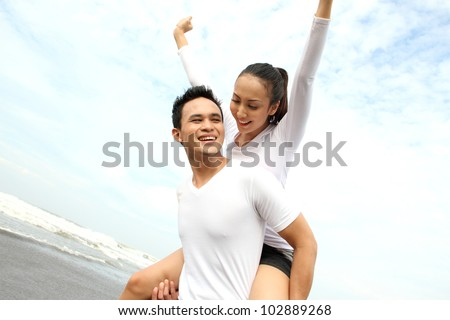 Portrait of a happy young couple having fun on the beach