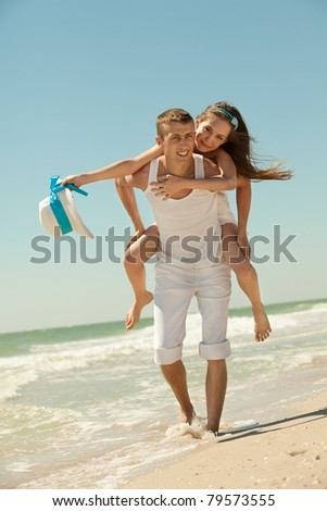Portrait of a happy young couple having fun on the beach. Young man giving piggyback to woman on beach.Couple enjoying a summer vacation.